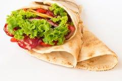 Rollen Sie Tortilla mit Kräutern, Käse und Fleisch auf weißem Hintergrund Lizenzfreie Stockfotos