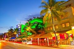 Rollender Verkehr, belichtete Hotels und Restaurants bei Sonnenuntergang auf Ozean fahren Stockbild