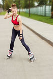 Rolleneislaufmädchen im Park, der auf Inline-Rochen rollerblading ist Mischrennen asiatische chinesische/kaukasische Frau in den  stockbilder