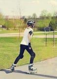 Rolleneislaufmädchen im Park, der auf Inline-Rochen rollerblading ist Mischrennen asiatische chinesische/kaukasische Frau in den  Lizenzfreies Stockbild
