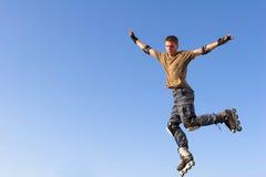 Rollenjunge, der vom Geländer auf dem blauen Himmel springt Lizenzfreies Stockfoto