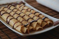 Rollenpfannkuchen mit Schokolade auf der Platte lizenzfreie stockfotos