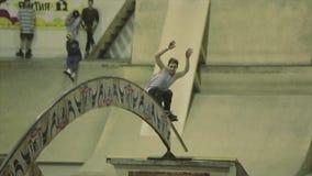 Rollenschlittschuhläuferschleifen auf gebogenem Bogen zwischen Sprungbrettern schwerpunkt extrem Wettbewerb im skatepark stock video footage