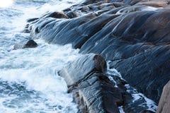 Rollenwelle, welche an die Felsen zuschlägt Stockbilder