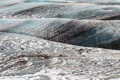 Rollenwellen eines blauen Gletschers mit diagonalen schwarzen Streifen und stockfotos
