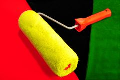 Roller. Yellow Roller On Black, Red And Green Background Stock Photography