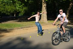 Roller and bicyclist on Hyde Park, London. Royalty Free Stock Photography
