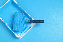 Roller with blue paint Stock Images