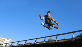 Roller boy jumping from parapet Royalty Free Stock Images