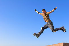 Roller boy jumping from parapet stock photography