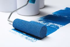 Roller brush with blue paint near cans. On white background stock images