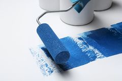 Roller brush with blue paint near cans on white. Background stock photo