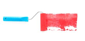 Roller brush with red paint on white background. Top view stock photo