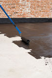 Roller brush waterproofing. Roller brush. Worker covered surface, bitumen primer for improving adhesion during surfacing, rolled waterproofing, during the Stock Photo