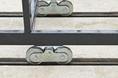 Roller caster. Metal roller caster installed at metal fence stock image
