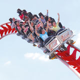 Roller coaster ride. People enjoying a roller coaster ride at a  theme park