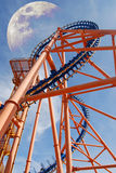 Roller-coaster. The structure of a roller coaster under a blue sky and the moon Stock Photos