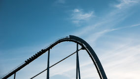 Roller coaster against blue sky. A roller coaster going up the tracks against a blue sky Royalty Free Stock Images