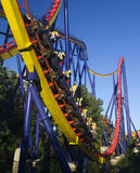 Roller coaster in amusement park. Tall roller coaster in amusement park going up a hill stock image