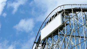 Roller coaster and blue sky. A roller coaster construction against blue, cloudy sky. A white blank board attached to it royalty free stock photo