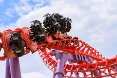 Roller coaster con el montar a caballo del sitio vacío a lo largo de la pista en el parque de atracciones Imágenes de archivo libres de regalías