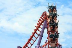 Roller coaster con la gente que monta a lo largo de la pista en el parque de atracciones Imagen de archivo libre de regalías