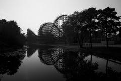 Roller coaster de madera, árboles y un lago Imagen de archivo