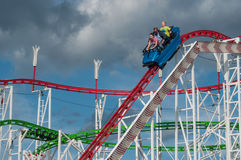 Roller coaster with shouting people in attraction park in Mulhouse. MULHOUSE - France - 25 July 2017 - roller coaster with shouting people in attraction park in Royalty Free Stock Photography