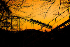 Roller coaster train is going up at autumn sunset. Color photo of a roller coaster train is going up at autumn sunset Royalty Free Stock Image