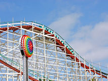 Roller Coaster Under Blue Skies. Bright colored roller coaster under blue skies with white clouds at an amusement park Stock Photos