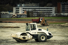 Roller compactor industrial vehicle car. Construction site. A roller compactor car parked in industrial construction site. In the distance other industrial Stock Photos