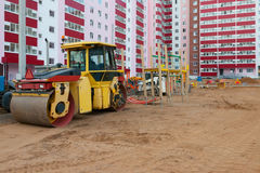 Roller at construction site next to new building and playgro Stock Photography