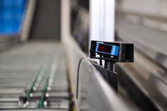 Roller conveyor with laser distance sensor. Stock Photos