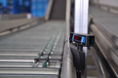 Roller conveyor with laser distance sensor. Close up shot of a roller conveyor with a laser distance sensor on the side. Photo taken in a big warehouse Royalty Free Stock Image