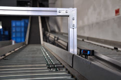 Roller conveyor with laser distance sensor. Royalty Free Stock Photo