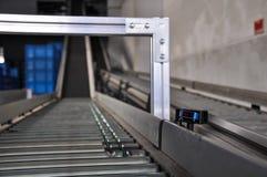 Roller conveyor with laser distance sensor. Royalty Free Stock Photo