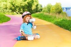 Roller de garçon et eau de boissons de bouteille Photographie stock