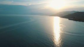 Roller, der auf Vogelperspektive 4K Schwarzen Meers fährt Über das Meer hoch fliegen, welches die Sonne gegenüberstellt stock footage