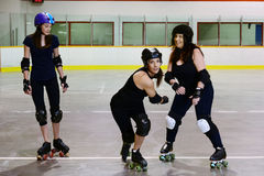 Roller derby girls focus on center skater. In an arena royalty free stock photo