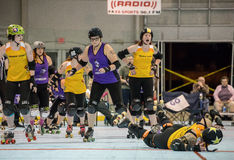 Roller Derby Girls Going Down. Redding, California-February 21, 2015: Lava City girls (yellow) fall to the floor during a flat track bout with the Shasta Roller royalty free stock photography