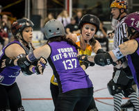 Roller Derby Girls Jamming. Redding, California-February 21, 2015: Shasta girls ( purple) set up a block on the Lava City girls during  flat track bout with the Stock Images