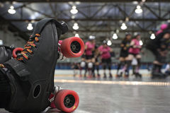 Roller derby skater fall. An abstract image of the roller-skates of a fallen skater as her teammates in the background continue to skate around the track of the
