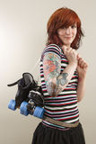 Roller derby skater girl. Photograph of a roller derby girl holding her skates by the laces royalty free stock photography