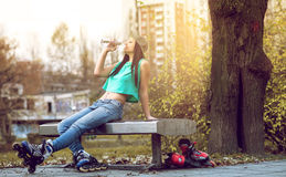 Roller girl drinking water on bench Royalty Free Stock Photo