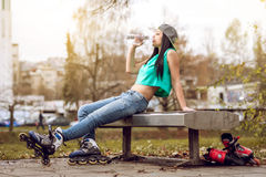 Roller girl drinking water on bench Stock Image