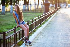Roller girl wearing jeans sitting on iron fence Royalty Free Stock Photo