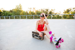 Roller girl in red swimsuit listening music with record player Stock Images