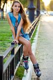 Roller girl wearing jeans sitting on iron fence Royalty Free Stock Photography
