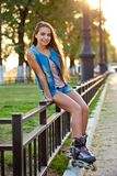 Roller Girl Wearing Jeans Sitting On Iron Fence Stock Image