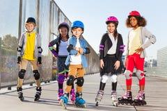 Roller heureux d'écolier avec des compagnons dehors Photo libre de droits